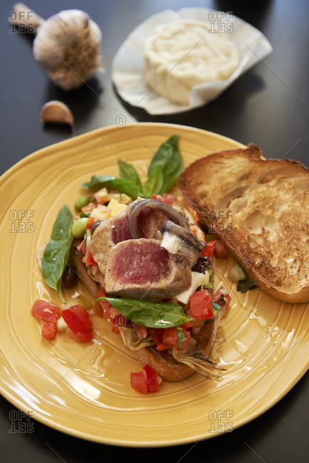 True nicoise salad with fresh tuna tataki on toasted bread, garlic and goat cheese