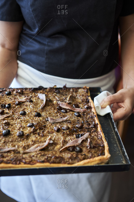 Chef holding a pissaladiere kind of nicoise pizza with onions and anchovies confit