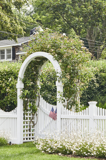 Beautifully manicured yard with white picket fence with trellis arch