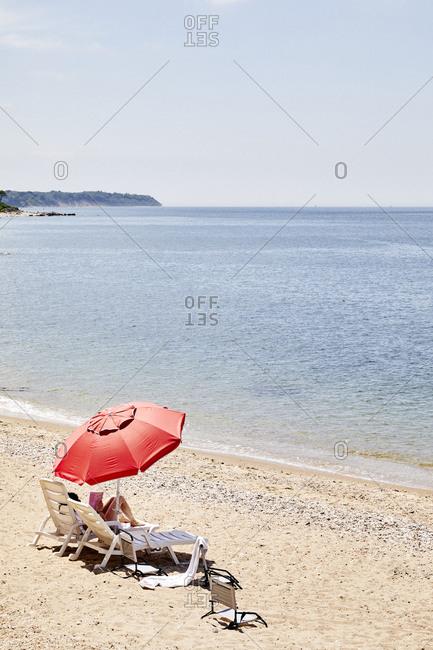 North Fork, Long Island - July 5, 2019: Woman sunbathing and reading a magazine on New Suffolk Beach