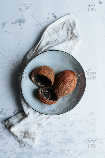 Coconuts in a bowl on light surface
