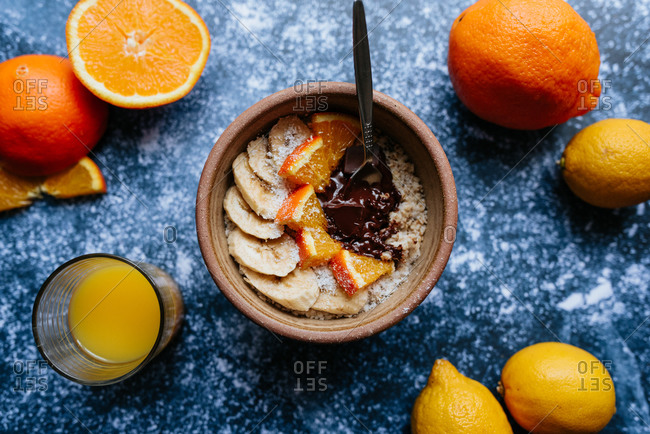 Overhead view of oatmeal with chia seed, bananas and oranges