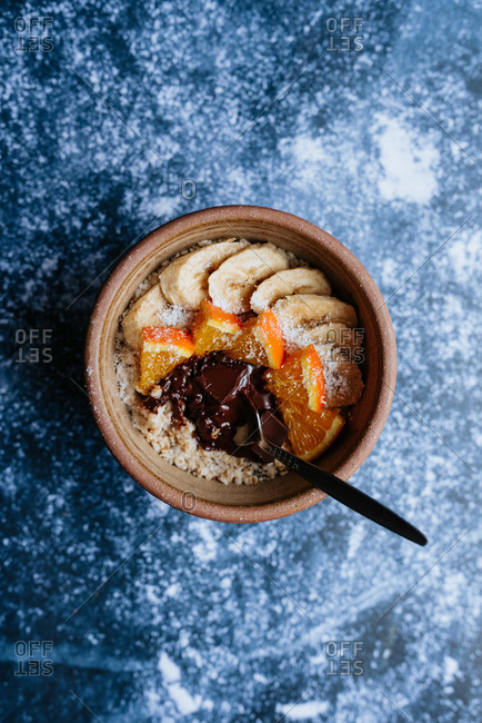 Oatmeal with chia seed, bananas and oranges on blue background