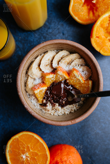 Oatmeal with chia seed, bananas and oranges on blue background from above