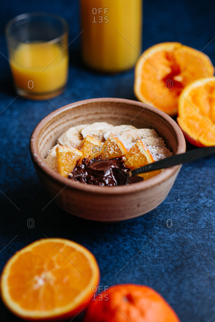 Fresh made oatmeal with chia seed, bananas and oranges