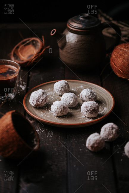 Fresh homemade coffee beside a plate of raw coconut and date balls