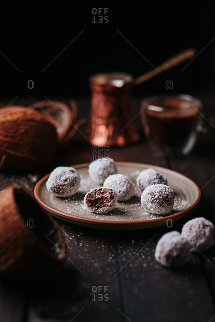 Raw coconut and dates balls with homemade coffee on a rustic wooden table