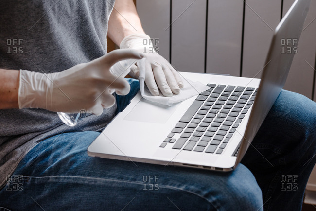 Person disinfecting computer while wearing gloves