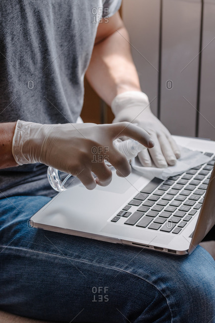 Person wiping disinfectant onto computer while wearing gloves