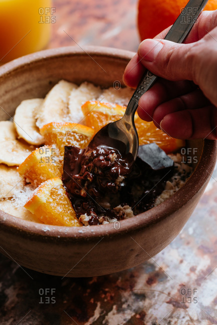 Person eating oatmeal with chia seed, bananas and oranges