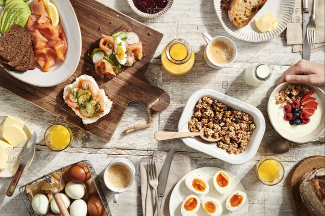 Breakfast table with rye bread, smoked salmon, boiled eggs, granola, coffee and orange juice