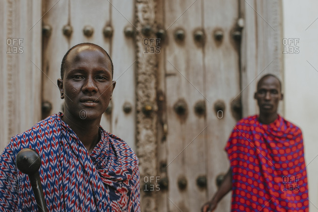 Two masai men standing in front of a traditional door in old town
