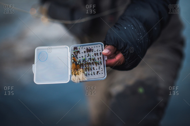 A man picks his flies during a cold morning fishing in Maine