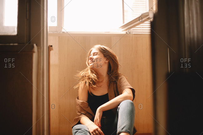 Young woman tossing hair while sitting on floor in balcony in summer