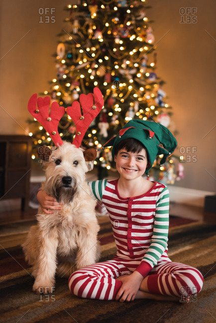 Boy in elf hat and dog in antlers sitting in front of Christmas tree.