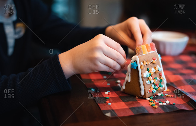 Close up of child's hands putting candies on a gingerbread house.