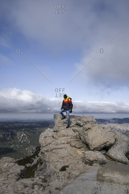 Men sitting above the clouds among the mountains