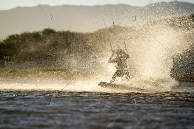 Young female athlete kiteboarding at sunset in La Ventana, Mexico