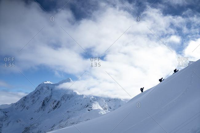 Men climbing mountain to ski in backcountry at Mt. Baker, Washington