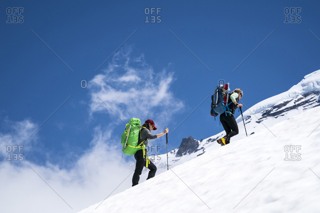 Two female mountaineers hike above cloudline on Mt. Baker, WA