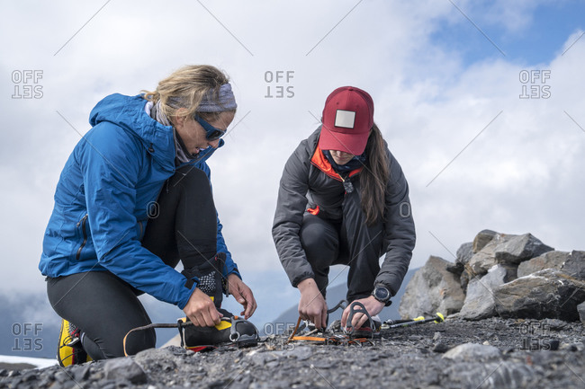 A female mountaineer explains how to put on crampons at base camp, Mt. Baker