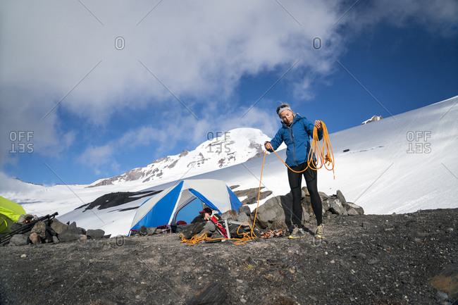A female mountaineer winds her rope in front of her tent at base camp, Mt. Baker