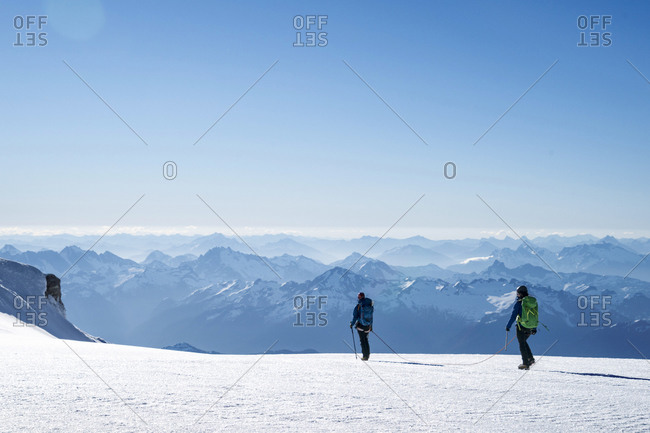 Two female mountaineers make their way across a glacier on Mt. Baker