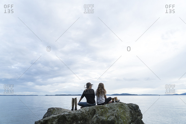Two friends sit on a rock with their shoes beside them looking out over the water