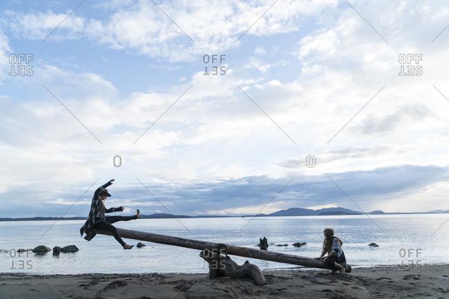 Two teenage girls using a log as a seesaw on Clayton Beach