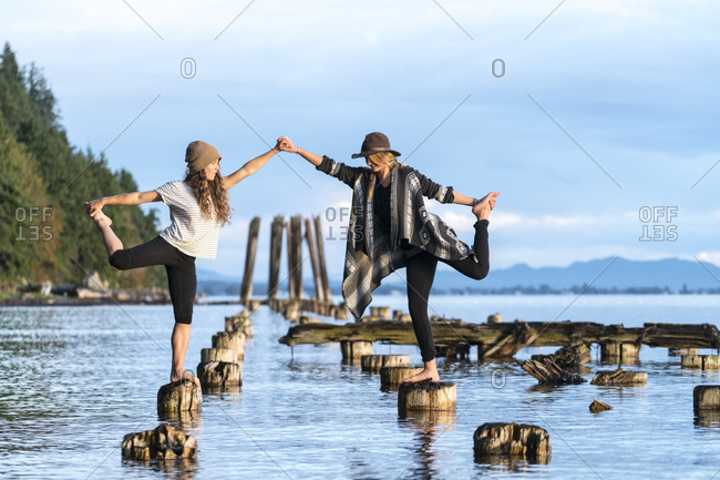 Two women do yoga on the remains of an old pier in Bellingham, WA