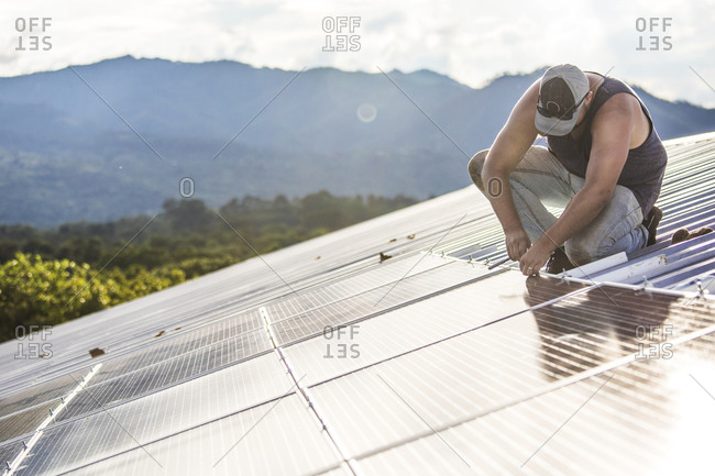 Worker installs solar panels on roof of building.