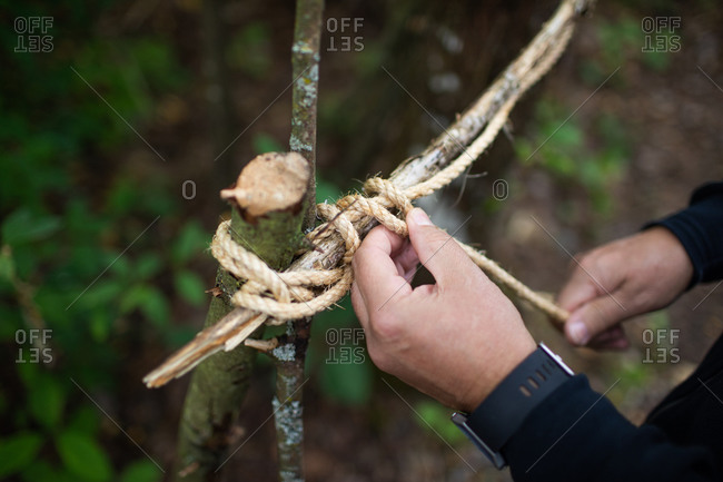 Man ties sticks together with twine to make tree fort.