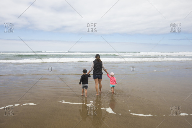 Rear view of mother walking toward ocean holding hands of her two kids