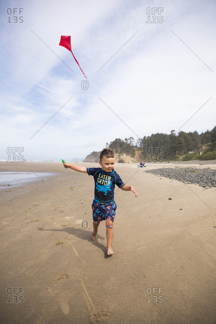 young boy running with kite on Oregon Coast beach.
