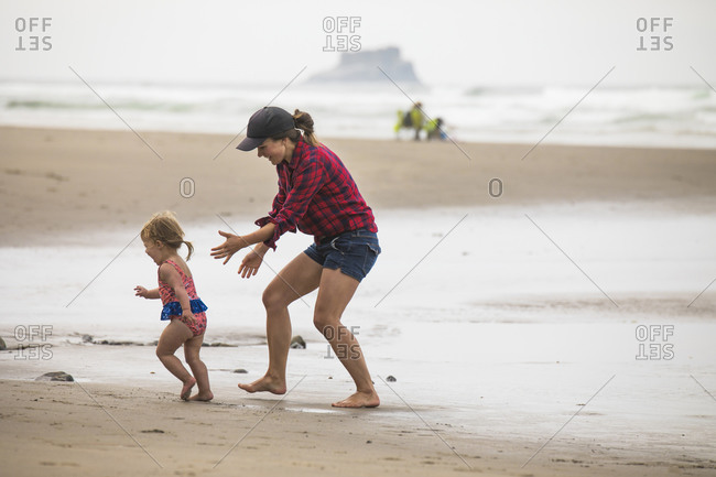 Fit, fun mother playfully chases her young daughter on the beach.