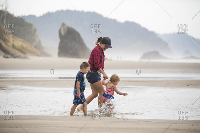 Side view of mother walking at beach with her two young kids.