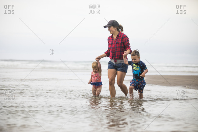 Mother wading into the ocean with her two children.