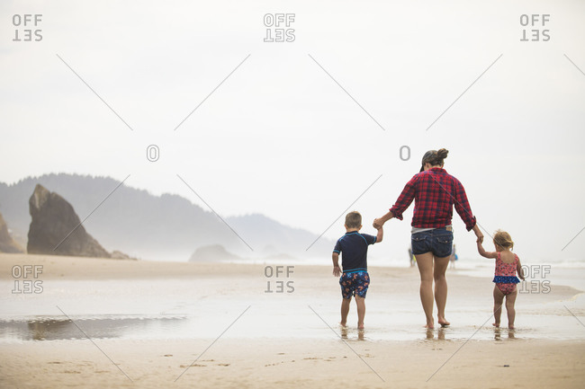 Rear view of mother walking on beach with her two young children.
