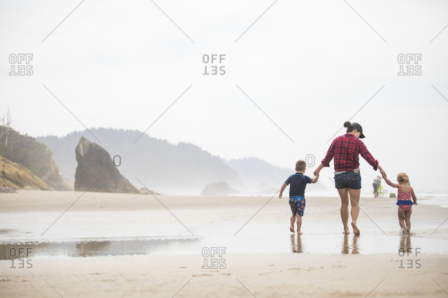 mother walking on beach with her two young children.