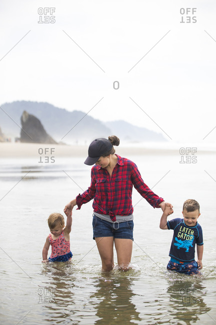 Mother wades through water with her two kids.