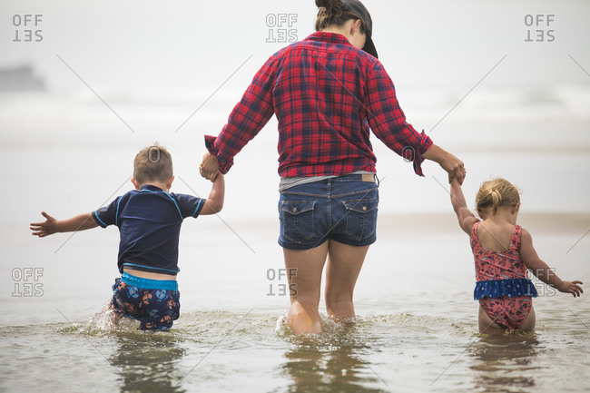 rear view of mother helping kids wade through water at the beach.