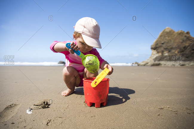 Young girl shoveling sand into bucket at the beach.