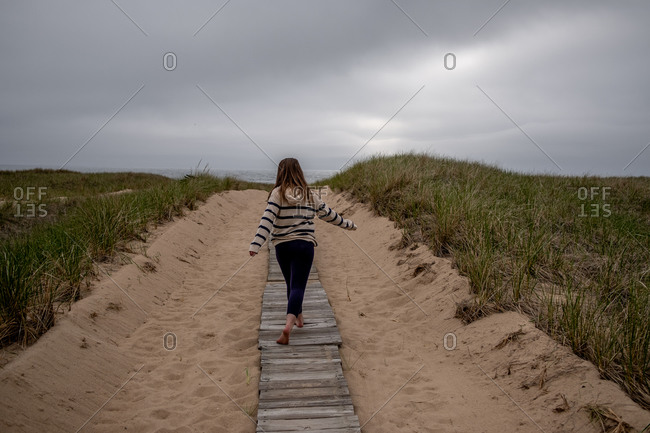 View from behind as girl walks down board walk to Lake Michigan