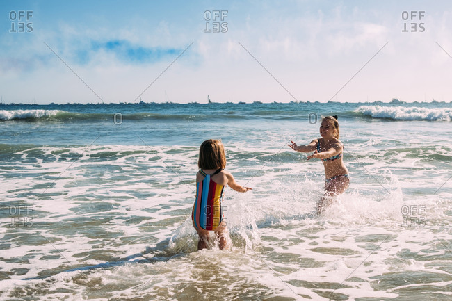 Sisters playing and splashing in the pacific ocean