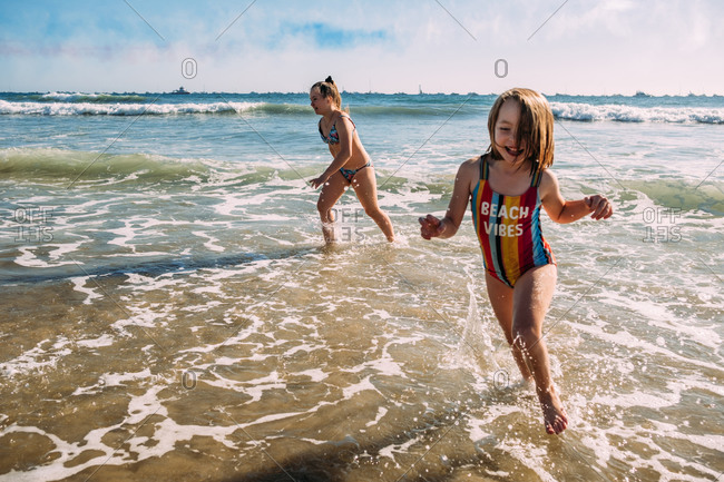 Sisters running on beach and splashing in water