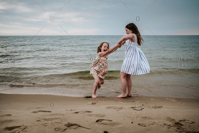 Older sister swinging younger sister on the beach at Lake Michigan