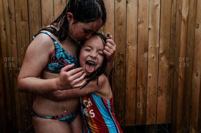 Girls hugging and being silly in outdoor shower