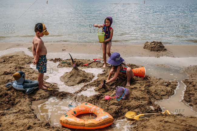 Young children building sand castles on a beach in summer