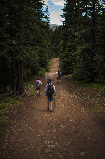 Father and two teen sons walking on trail after fishing in the Canadian Rockies