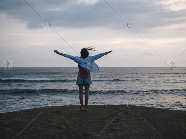 Woman with raised arms standing at the sea at sunset